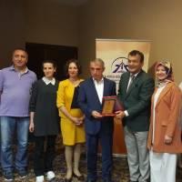 Hasan Uzunhasanoğlu Başkanlığındaki Akça Koca Kültür Platformu Yöneticileri, Körfez Kaymakamı Dr. Hasan Hüseyin Can'a teşekkür plaketini takdim ederken
