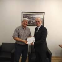 Ahsen Okyar, Özgür Kocaeli Gazetesi Genel Yayın Yönetmeni Adem Turgut'a, Dr. Nuri Çağlar'a vefa toplantısı davetiyesini takdim ederken