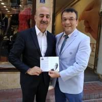 Hasan Uzunhasanoğlu, Biz İzmitiz Platformu Başkanı Hüseyin Erol'a, Dr. Nuri Çağlar'a vefa toplantısı davetiyesini takdim ederken