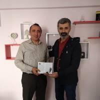 Yunus Özen, EN Kocaeli Genel Yayın Yönetmeni Engin Şahin'e, Dr. Nuri Çağlar'a vefa toplantısı davetiyesini takdim ederken