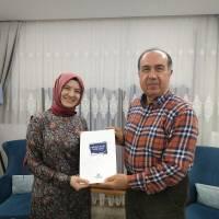 Dr. Ayşe Zeynep Turan, e. Avrupa Birliği Bakan Yardımcısı Dr. Alaattin Büyükkaya'ya Platformun yeni çıkan kitabını takdim ederken