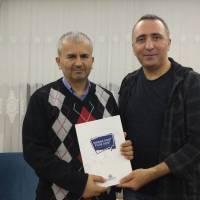 Yalova Üniversitesi Öğretim Üyesi Dr. Yunus Özen, Dr. Hasan Dermenci'ye platformun kitabını takdim ederken
