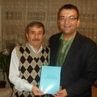 Av. Zeki Hacıibrahimoğlu son hazırladığı kitabını imzalayıp Hasan Uzunhasanoğlu'na diş kirası olarak takdim ederken