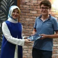 Okan Üniversitesi Hukuk Fakültesini kazanan Mehmet Maçil'e, Platform Yöneticisi Dr. Ayşe Zeynep Turan hediyesini verirken