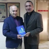 """Dr. Yunus Özen, Çağdaş Kocaeli Gazetesi Genel Yayın Yönetmeni Sadun Çetin'e davetiye ve Dr. Alaattin Büyükkaya'ya ait """"Yalnız Yürümeyeceksin"""" kitabını takdim ederken"""